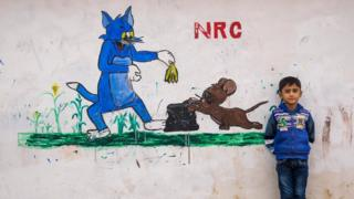 A child in Domiz Syria refugee camp in 2014 stands next to a mural of Tom and Jerry