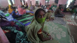 Evacuated people sit in a temporary cyclone relief shelter as Cyclone Ampha