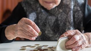 Imagem mostra mulher idosa contando dinheiro