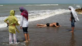 Women paddle in the sea fully-clothed while a man in swimming pants rests on the sand on 10 July 2005