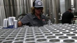 Kathryn Fisher with Can Van, a mobile canning company, places empty aluminum cans on a conveyor belt to be filled with beer at Devil's Canyon Brewery on June 6, 2018 i
