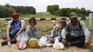 Migrants from Syria sit on a dam near Szeged, southern Hungary, 29 Jun 15
