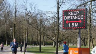 People running pass a sign urging people to practice social distancing in Amsterdam