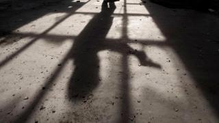 Тень человека с пистолетом