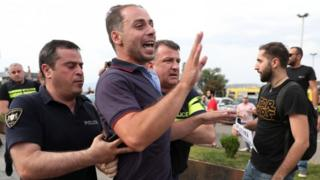 Police arrest a man at a protest in Tbilisi
