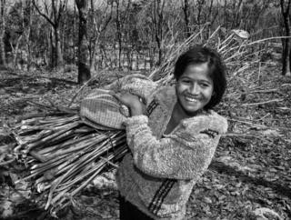 A girl carries a bundle of sticks
