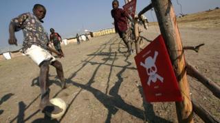 Angola'da mayınlı arazinin hemen yanında futbol oynayan çocuklar