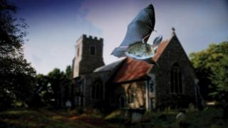 Bat flies past a church
