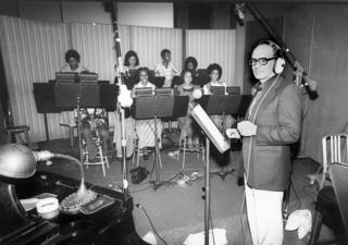 Morricone with singers in a recording studio
