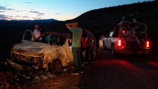 Miembros de la familia LeBarón observan el automóvil quemado donde viajaban algunas de las nueve víctimas asesinadas en México
