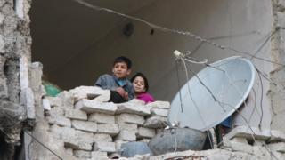Мальчик девочка выглядывают из окна полуразрушенного дома в Алеппо