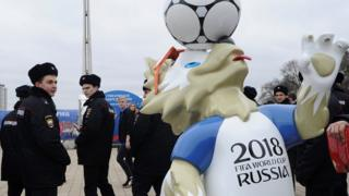 Police officers walk past the official mascot for the 2018 FIFA World Cup Russia, Zabivaka during the opening of the Football Park in Rostov-on-Don, Russia March 31, 2018