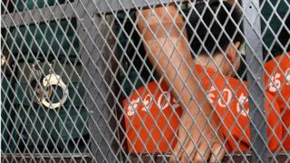 Cambodian Oeuth Ang, in prison uniform and facing away from the camera, behind the a police van wire mesh, outside court in Phnom Penh, Cambodia, 23 March 2017.