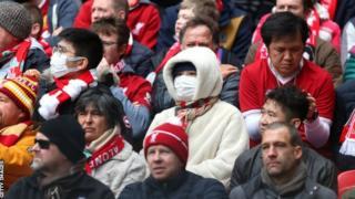 Fans uses masks at a Premier League game