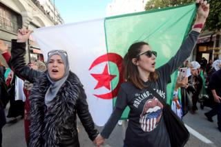 in_pictures Women carry a national flag during a march in Algiers, Algeria - Sunday 8 March 2020