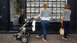 women looking in estate agent window