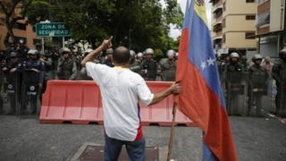 Manifestante opositor a Maduro frente a la Policía Nacional Bolivariana