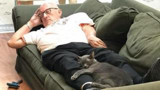 Terry lies on a sofa with a grey cat curled around his legs
