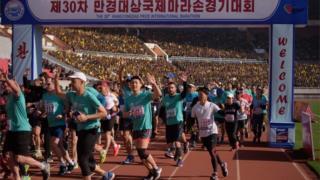 International runners cross the Pyongyang marathon starting line, waving crowds at Kim II Sun's stadium