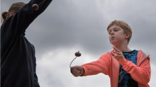 A boy wearing an orange jumper concentrates as he aims his conker.