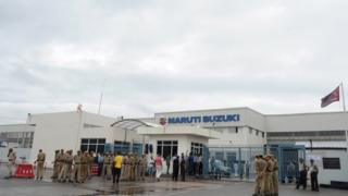 Private security guards stand guard at the main gate of the Maruti Suzuki Production Facility in Manesar