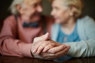 Una pareja, el hombre besa en el cachete a la mujer.