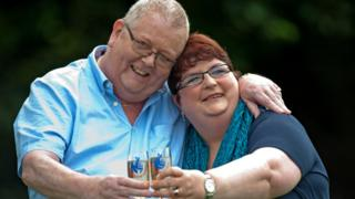 Colin Weir (L) and his wife Chris pose for pictures with champagne during a photocall in Falkirk, Scotland, on July 15, 2011, after winning a record GBP161m (