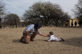 El hijo mayor de Oscar. Cristobal, en el corral con su hijo de ocho meses.