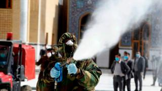 A member of the Iraqi civil defense sprays disinfectant on and around the Great Mosque of Kufa