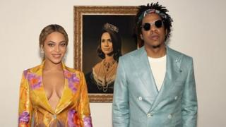 Image of Beyonce and Jay-Z in front of a portrait of Meghan Markle