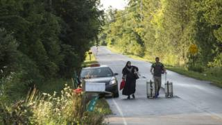 A cab drops off a couple of asylum seekers at the US/Canada border near Champlain, New York