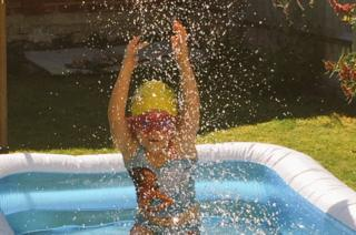 Young girl splasshing in a paddling pool