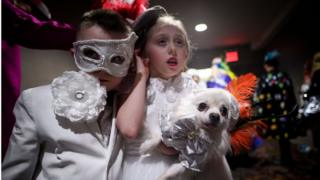 Two children dressed in white with their lovely little dog