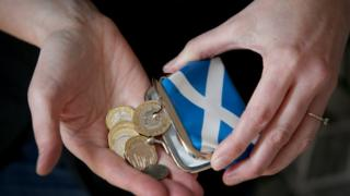 Pounds coins being tipped out of a purse with the flag of Scotland
