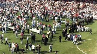 Hillsborough spectators run with makeshift stretchers on pitch
