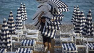 A man laying out cushions on beach sunbeds