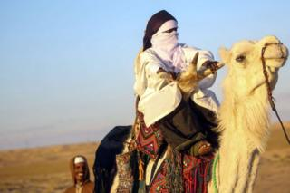A Tuareg tribesman rides a camel during a traditional ceremony in the Libyan desert in the western Awal region near the borders with Tunisia and Algeria, about 600km (373 miles) southwest of the capital, Tripoli, on 29 March 2019