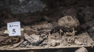"""A picture taken on May 13, 2017, shows a mummy lying in catacombs following its discovery in the Touna el-Gabal district of the Minya province, in central Egypt. Egyptian archaeologists have discovered 17 non-royal mummies in the desert catacombs, an """"unprecedented"""" find for the area south of Cairo, the antiquities ministry announced. Along with the mummies, they found a golden sheet and two papyri in Demotic - an ancient Egyptian script - as well as a number of sarcophogi made of limestone and clay."""