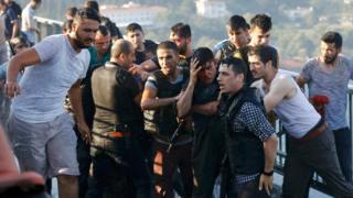 ポスポラス橋で投降した兵士を大統領支持者から守る警官たち(16日)