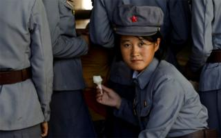 A soldier eats ice cream as she visits a zoo in Pyongyang, North Korea