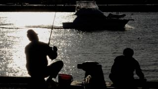 Fisherman sit and fish from the wharf of a Western Australian harbour