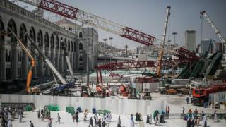 Muslim Pilgrims walk past the site of a crane collapse that killed more than 100 people at the Grand Mosque in the holy city of Mecca, Saudi Arabia (15 September 2015)