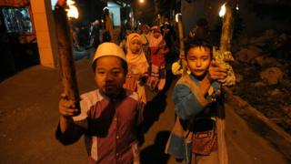 Children in Indonesia carry torches in a parade through the street to celebrate Eid al-Adha.