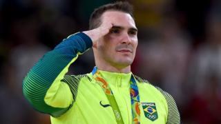 O ginasta e sargento Arthur Zanetti bate continência após receber medalha