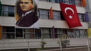 A portrait of Mustafa Kemal Ataturk hangs next to a Turkish flag on the outside of a religious school in Istanbul
