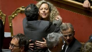 Italian senators hug after Thursday's vote