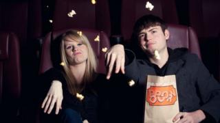 Dos jóvenes viendo una película con cara de total decepción