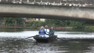 A three-rower team on a cot under bridge on the River Erne