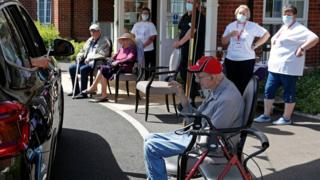 Staff look on as a visitor uses her phone to take a picture of her grandad during a drive-through visit at Gracewell, a residential care home in Adderbury near Banbury, west of London on May 28
