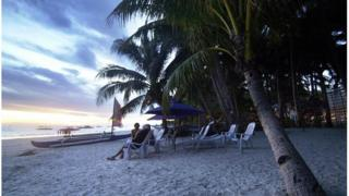 Tourist watch the sun set on the Philippine island of Boracay